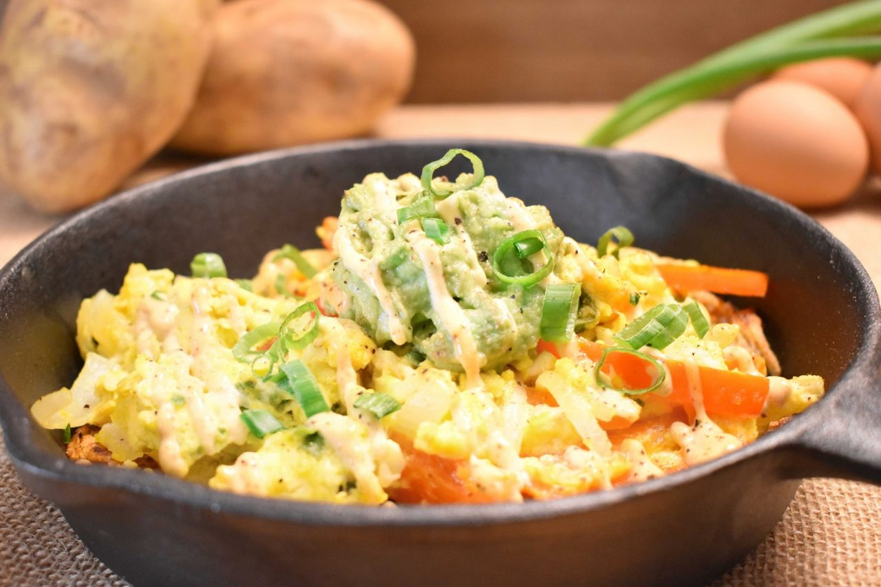 Sunshine Scramble in a cast iron skillet - Eggs, onions, red peppers, natural seasoning topped with fresh guacamole and chipolte aioli