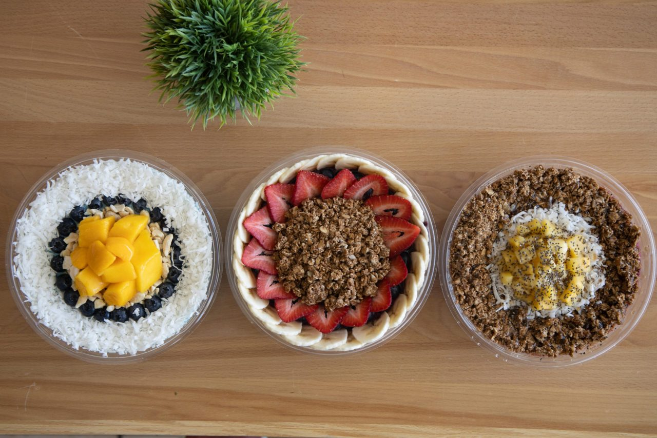 Three smoothie bowls on wooden counter