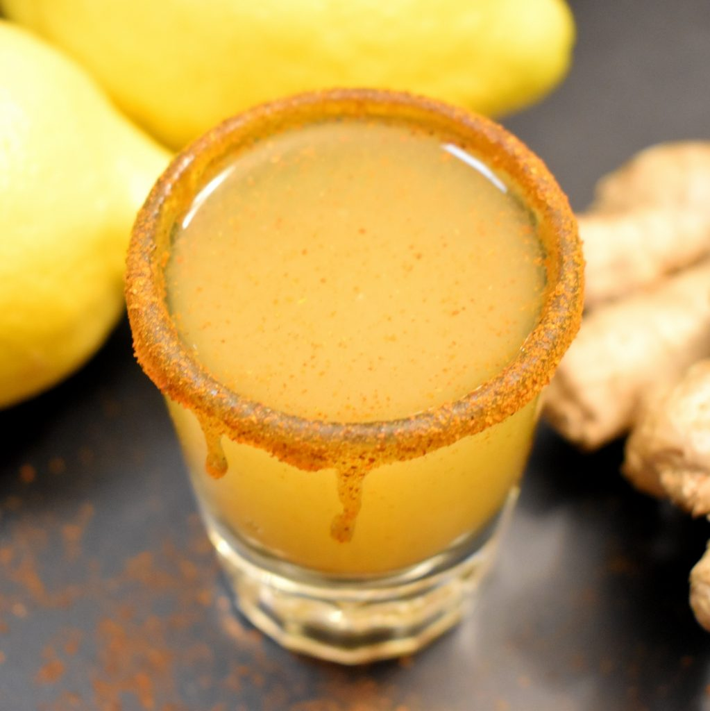 Orange colored wellness juice in a shot glass