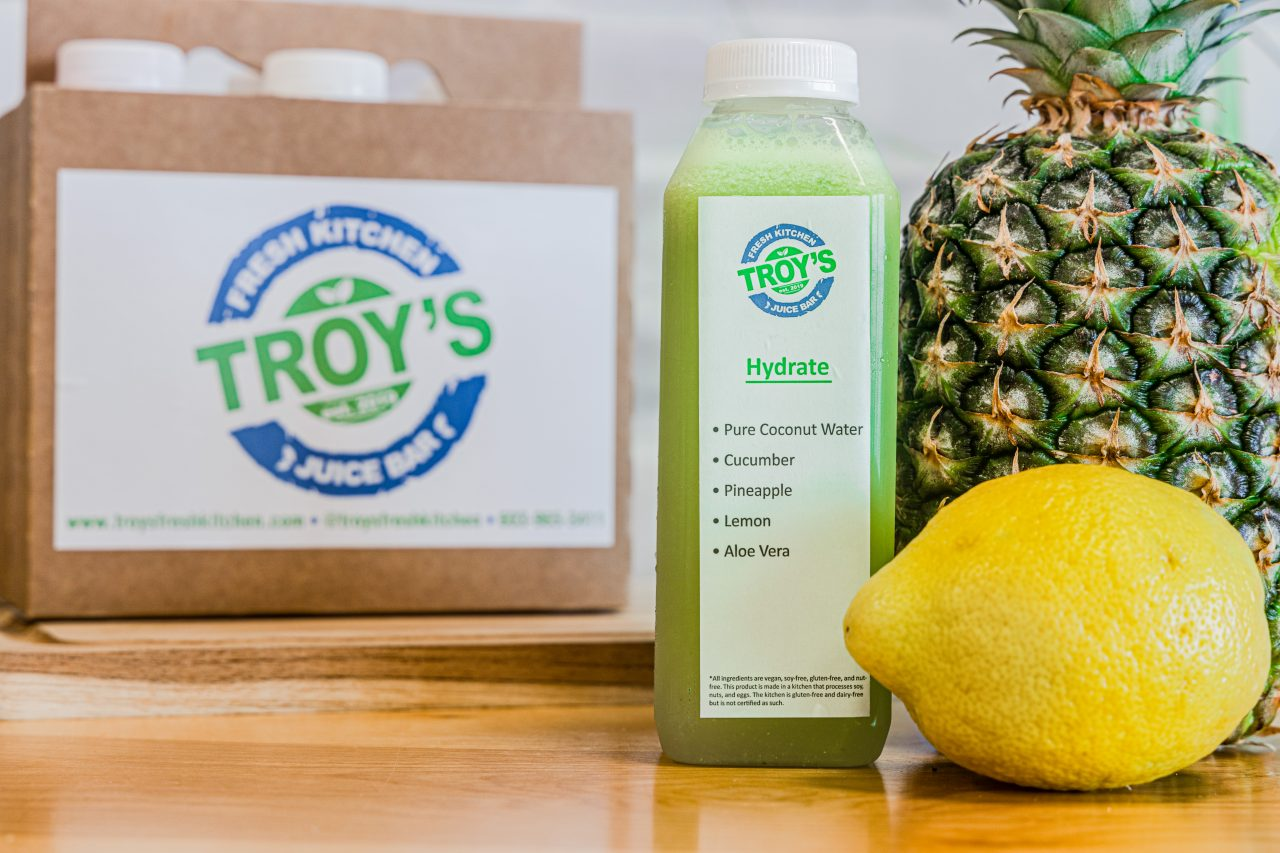 Custom Cleanse 6 pack featuring the Hydrate Juice with a lemon and a pineapple