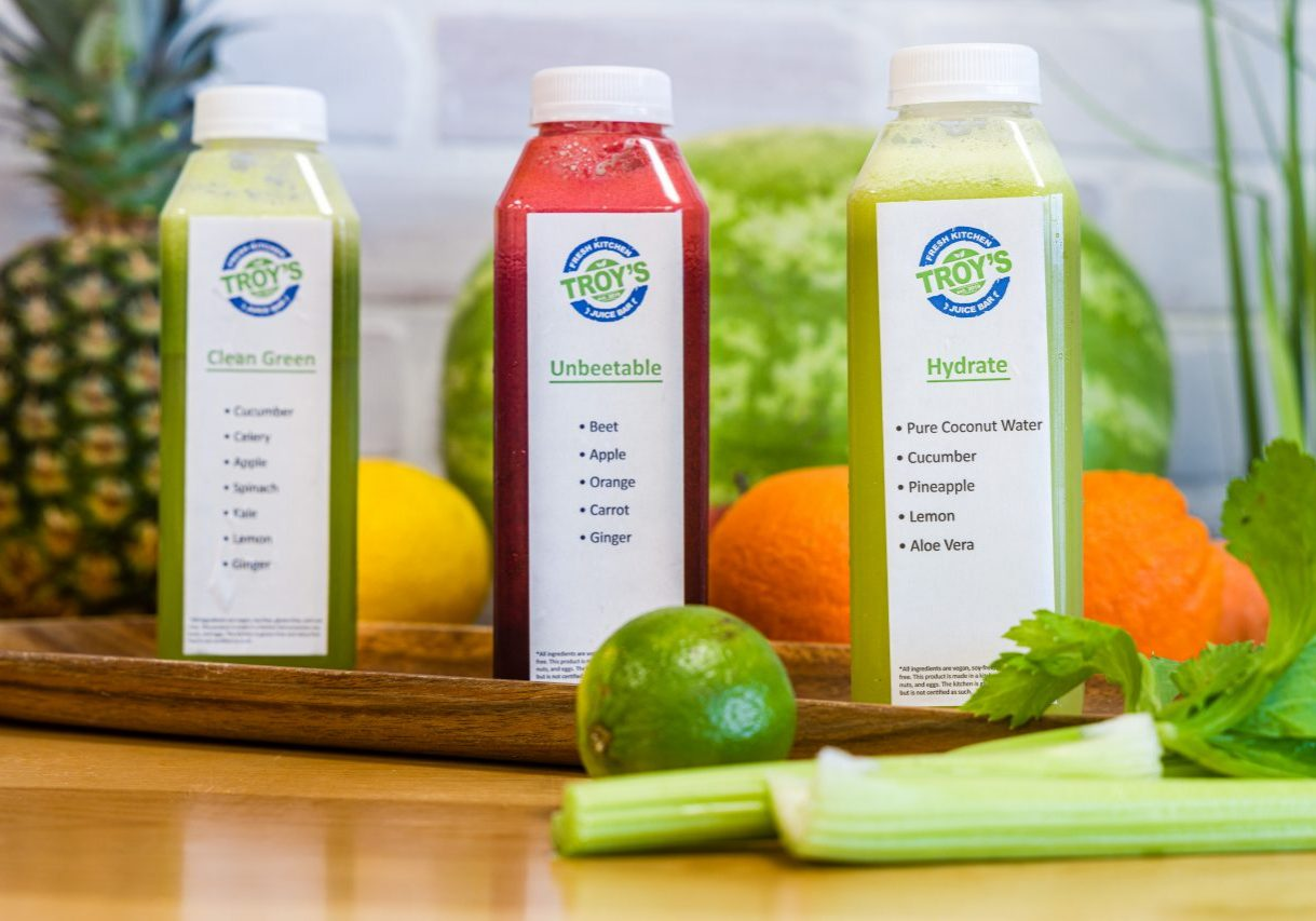 3 juice cleanse bottles surrounded by luscious fresh fruits and vegetables